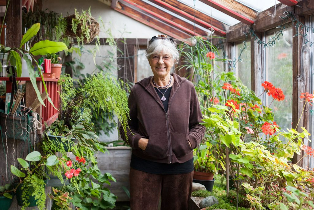 Anna Edey stands among the plants of her in-home greenhouse in West Tisbury, Massachusetts.